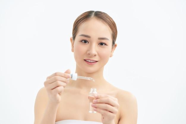 Portrait de jeune belle femme avec soins de la peau, produit de sérum sur fond blanc