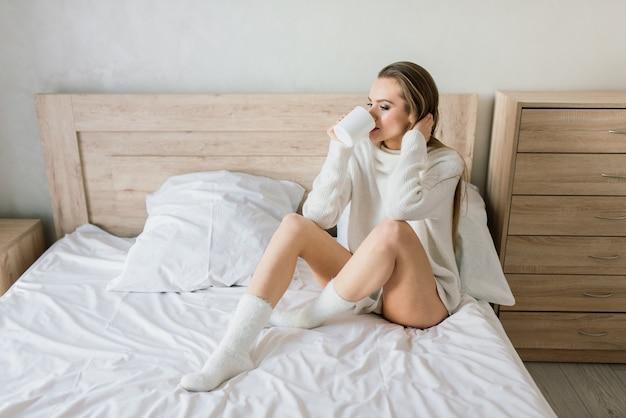 Portrait jeune belle femme souriante allongée dans son lit buvant son café du matin en rêvant. mine réjouie