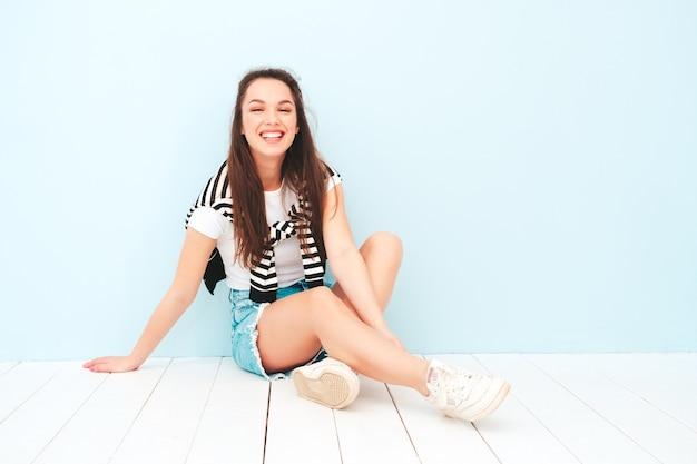 Portrait de jeune belle femme souriante dans des vêtements hipster d'été à la mode
