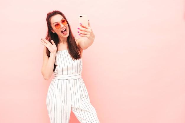 Portrait de jeune belle femme souriante dans des vêtements de salopette hipster d'été à la mode