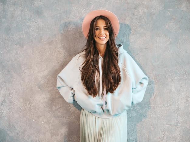 Portrait de jeune belle femme souriante à la recherche. fille à la mode dans des vêtements décontractés à capuche et jupe d'été.