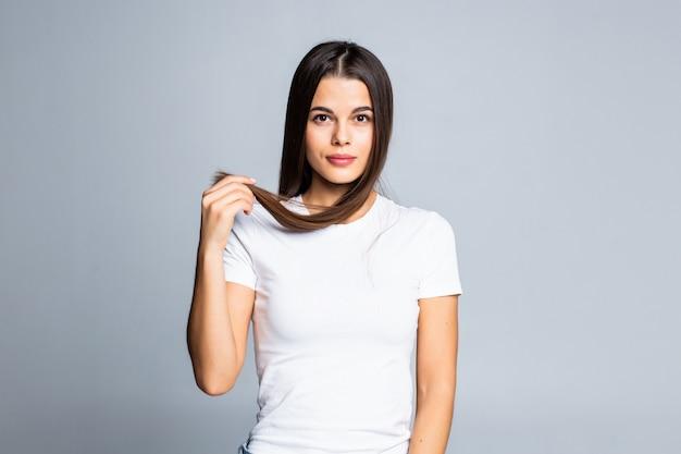 Portrait de jeune belle femme souriante tenant les extrémités de ses longs cheveux bruns sur blanc