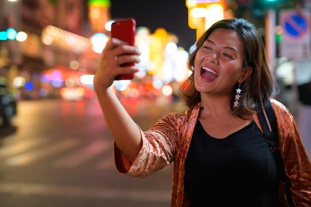 Portrait de jeune belle femme touristique asiatique à la découverte de chinatown à bangkok