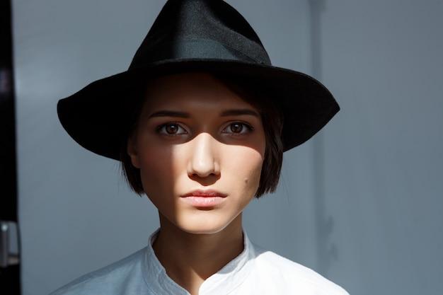 Portrait de jeune belle fille brune au chapeau noir.