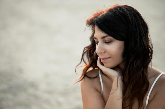 Portrait de jeune belle fille caucasienne aux cheveux en désordre, rêver