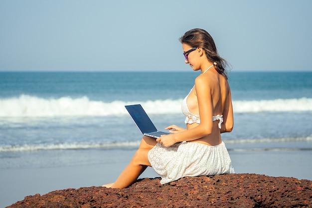Portrait d'une jeune et belle fille indépendante qui court sur la plage avec un ordinateur portable. femme d'affaires en vacances. concept de travail indépendant et de travail.