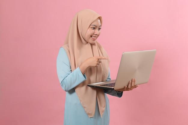 Portrait d'une jeune belle fille musulmane souriante tenant un ordinateur portable et pointant isolé sur fond rose.