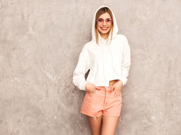 Portrait de jeune belle fille souriante dans des vêtements de sport d'été à la mode. sexy femme insouciante posant. modèle positif s'amusant dans des lunettes de soleil