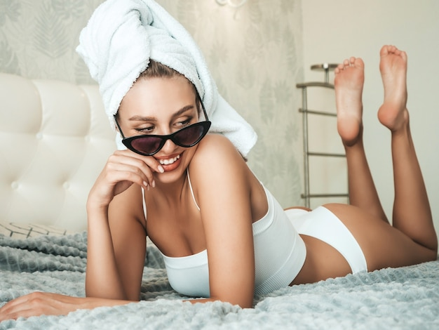 Portrait de jeune belle fille souriante en lingerie blanche et serviette sur la tête