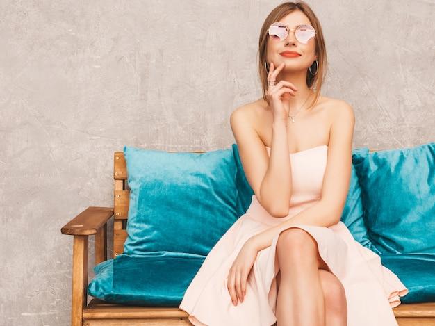 Portrait de jeune belle fille souriante en robe rose pâle d'été à la mode. sexy femme insouciante assise sur un canapé bleu vif. posant dans un intérieur de luxe