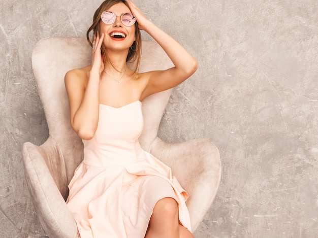 Portrait de jeune belle fille souriante en robe rose pâle d'été à la mode. sexy femme insouciante assise sur une chaise beige. posant dans un intérieur de luxe