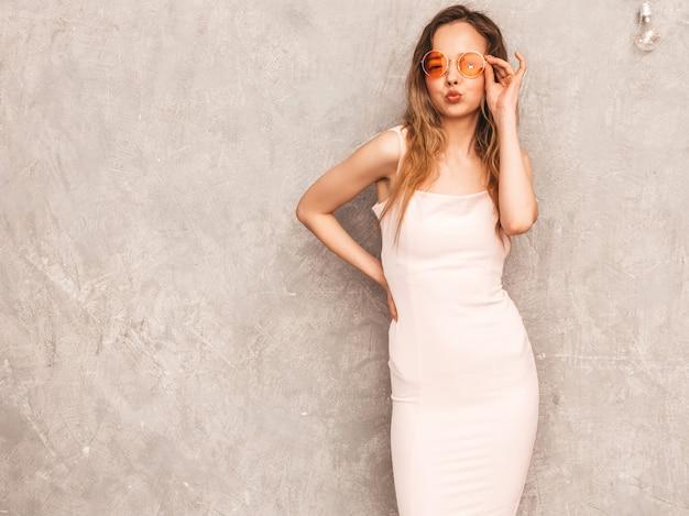 Portrait de jeune belle fille souriante en robe rose pâle d'été à la mode. sexy femme insouciante posant. modèle positif s'amusant dans des lunettes de soleil rondes