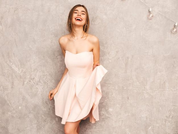 Portrait de jeune belle fille souriante en robe rose pâle d'été à la mode. sexy femme insouciante posant. modèle positif s'amusant