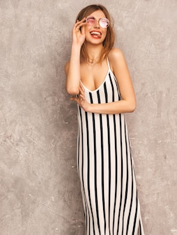 Portrait de jeune belle fille souriante en robe zèbre d'été à la mode. sexy femme insouciante posant. modèle positif s'amusant dans des lunettes de soleil rondes. un clin d'oeil