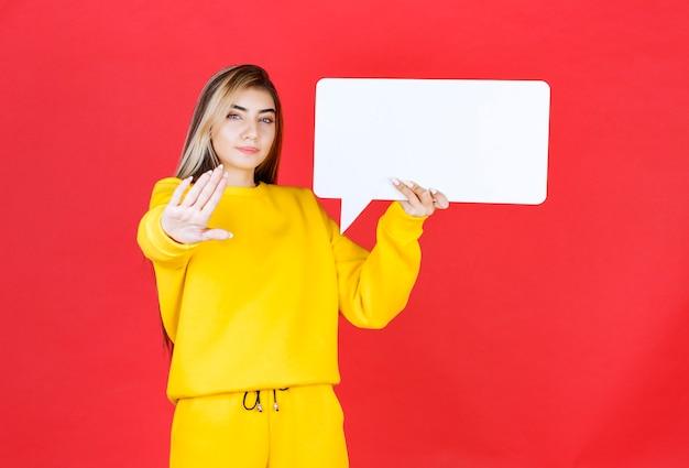 Portrait de jeune belle fille tenant un cadre de discours vierge sur un mur rouge