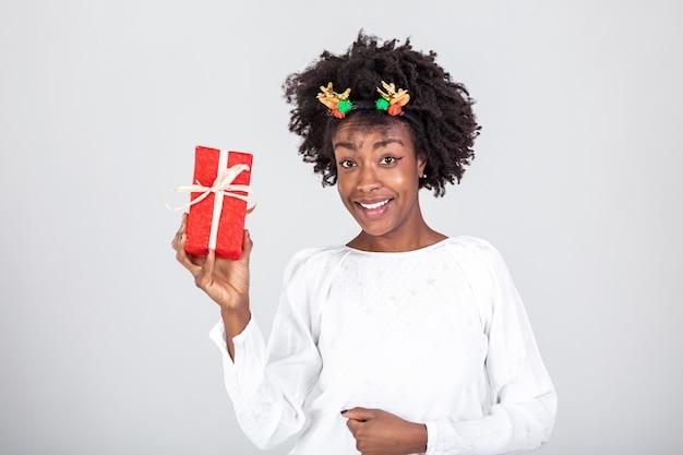 Portrait de jeune belle jolie fille noire glamour douce, portant une boîte-cadeau, s'interrogeant sur la surprise.