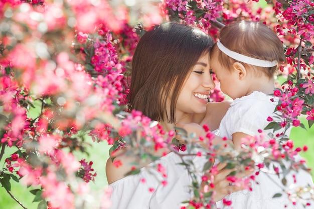 Portrait de jeune belle mère avec sa petite fille. gros plan d'une famille aimante. jolie femme tenant son enfant en fleurs roses et souriant.