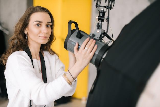 Le portrait de la jeune belle photographe de femme prépare la softbox d'équipement léger