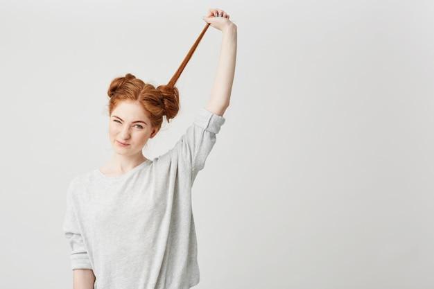 Portrait de jeune belle rousse dénouer chignon toucher les cheveux.