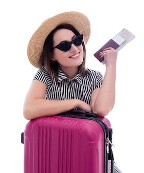 Portrait de jeune belle touriste de femme dans le chapeau de paille et les lunettes de soleil avec la valise, le passeport et la carte de ville d'isolement sur le fond blanc