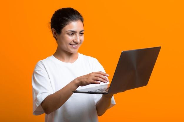 Portrait de jeune blogueuse indienne adulte souriante travaillant avec un ordinateur portable