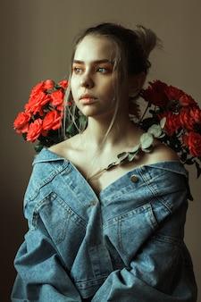 Portrait d'une jeune blonde avec du maquillage rouge dans une veste en jean et un bouquet de roses