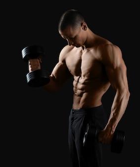 Portrait d'un jeune bodybuilder soulever des poids au studio sur fond noir