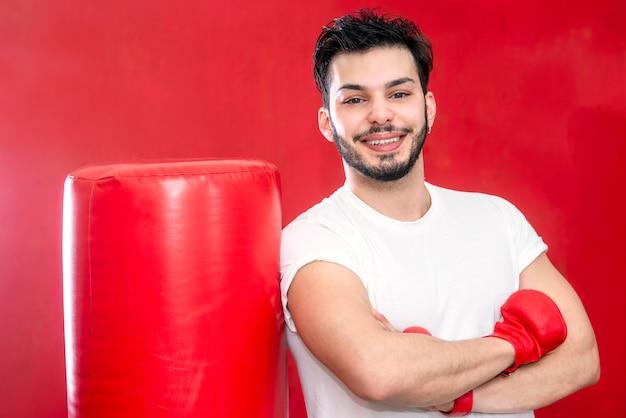 Portrait de jeune boxeur barbu souriant posant par sac de boxe dans un gymnase