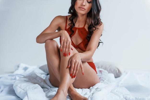 Portrait de jeune brune joyeuse qui est en sous-vêtements rouges assis sur le lit.