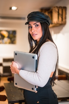 Portrait d'une jeune brune latine avec un ordinateur télétravaillant depuis une cafétéria en vacances
