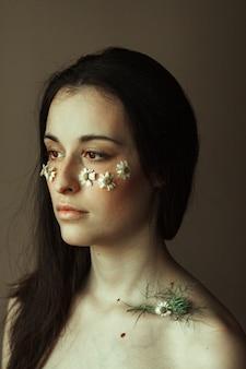 Portrait d'une jeune brune avec de petites marguerites sur ses joues et une tige verte sur la clavicule.