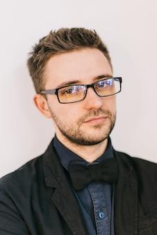 Portrait d'un jeune coiffeur à lunettes avec une coiffure et une cravate.