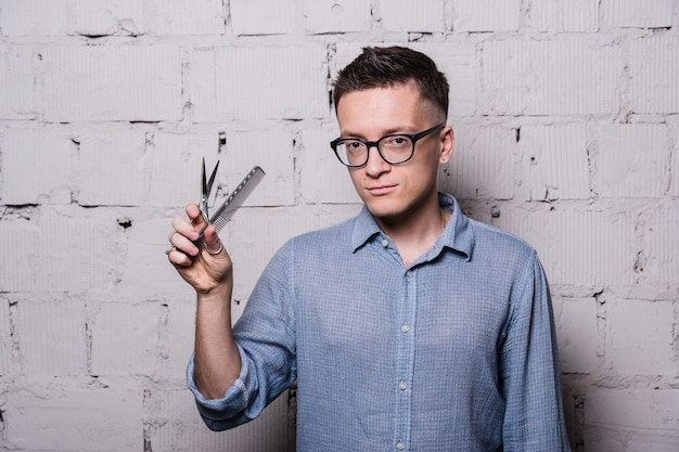 Portrait de jeune coiffeur masculin dans des verres, posant avec des ciseaux, sur le mur de briques grises