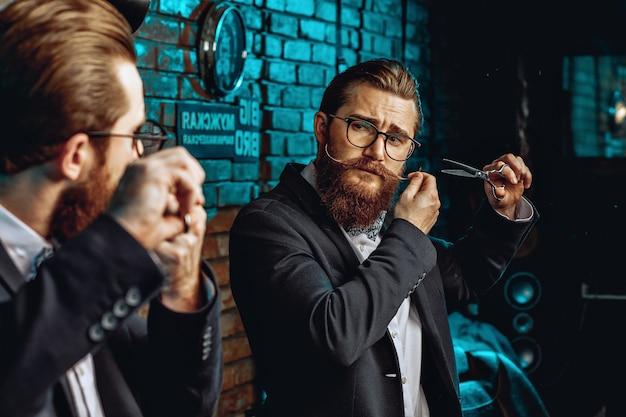 Portrait d'un jeune coiffeur masculin avec des lunettes, une moustache et une barbe tenant du matériel et des outils pour travailler avec les cheveux. concept de style