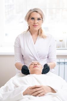 Portrait de jeune cosmétologue en gants noirs à l'aide d'un coton tout en nettoyant la peau du visage de femme mûre avant la procédure
