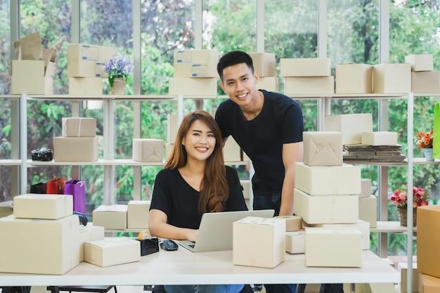Portrait de jeune couple d'affaires asiatiques heureux propriétaire de pme en ligne à la recherche de l'appareil photo