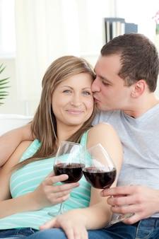 Portrait d'un jeune couple affectueux, boire du vin rouge