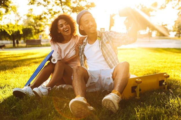 Portrait d'un jeune couple africain heureux avec des planches à roulettes