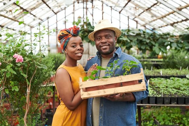 Portrait de jeune couple africain souriant à la caméra tout en plantant des semis dans la serre