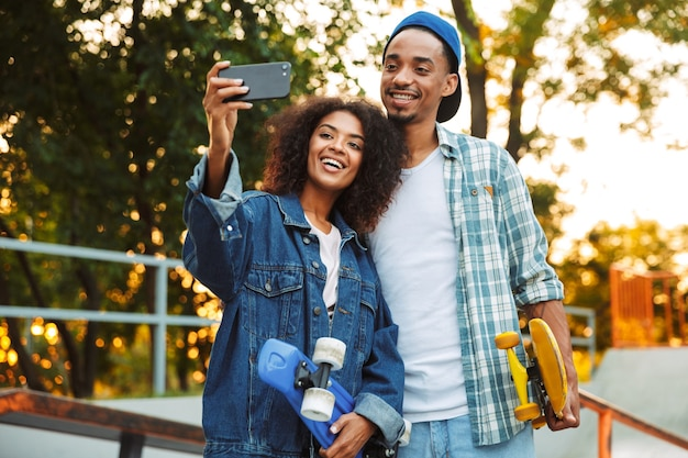 Portrait d'un jeune couple africain souriant avec des planches à roulettes