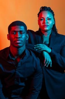 Portrait de jeune couple afro-américain amoureux posant vêtu de vêtements classiques. néon