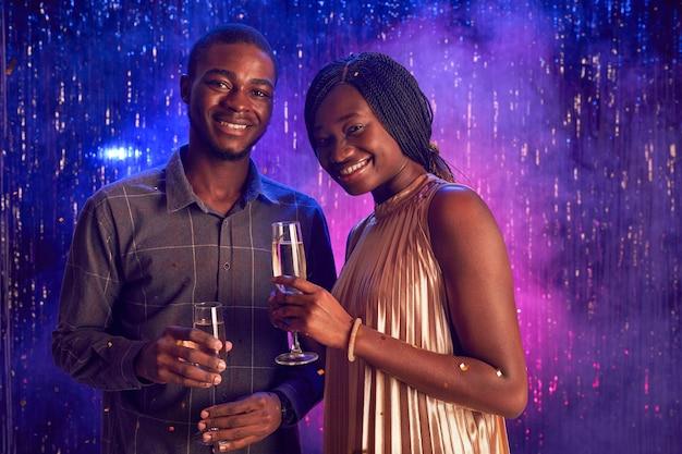 Portrait de jeune couple afro-américain tenant un verre de champagne et souriant à la caméra tout en profitant de la fête en discothèque, copiez l'espace