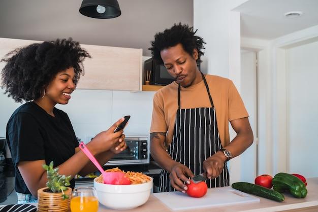 Portrait de jeune couple afro cuisiner ensemble dans la cuisine tandis que femme prenant des photos de nourriture avec téléphone à la maison