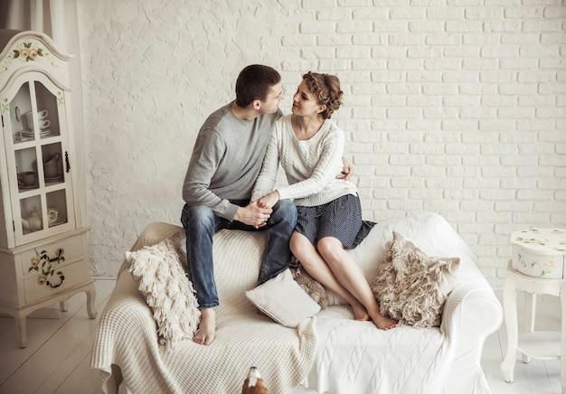 Portrait d'un jeune couple aimant assis sur un canapé dans la salle de séjour