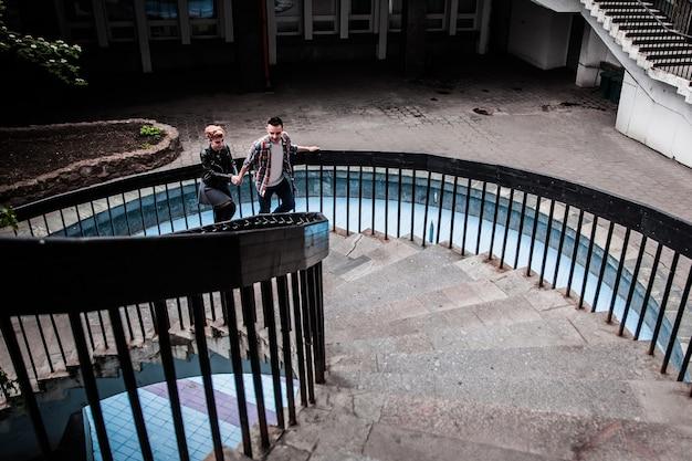 Portrait d'un jeune couple aimant en montant les escaliers dans une ville moderne. le concept de relations amoureuses