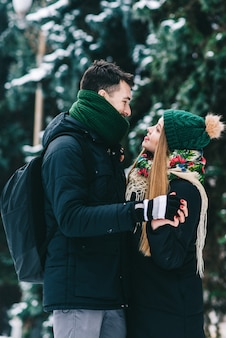 Portrait d'un jeune couple d'amoureux heureux qui se lie avec tendresse. ils se regardent et sourient en se tenant à l'extérieur en hiver