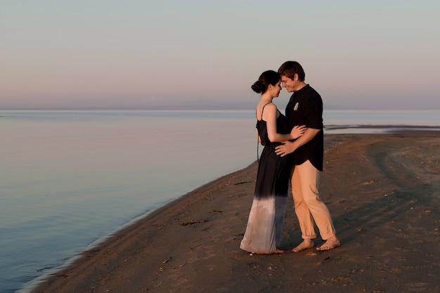 Portrait d'un jeune couple d'amoureux sur la plage à l'éclairage du coucher du soleil. espace de copie.