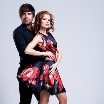 Portrait de jeune couple amoureux posant au studio habillé en vêtements classiques