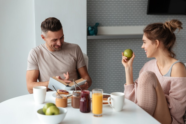 Portrait d'un jeune couple d'amoureux prenant son petit déjeuner