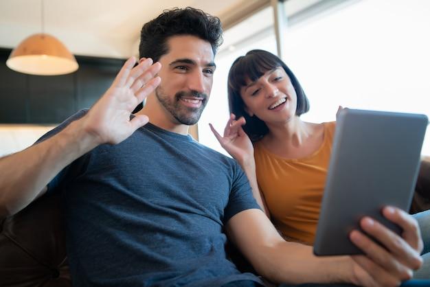 Portrait de jeune couple sur un appel vidéo avec tablette numérique alors qu'il était assis sur le canapé à la maison